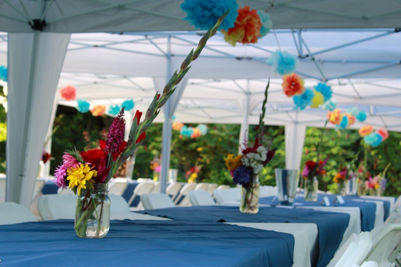 Tables with blue cloths and handpicked flower centrepieces ready for wedidng brunch