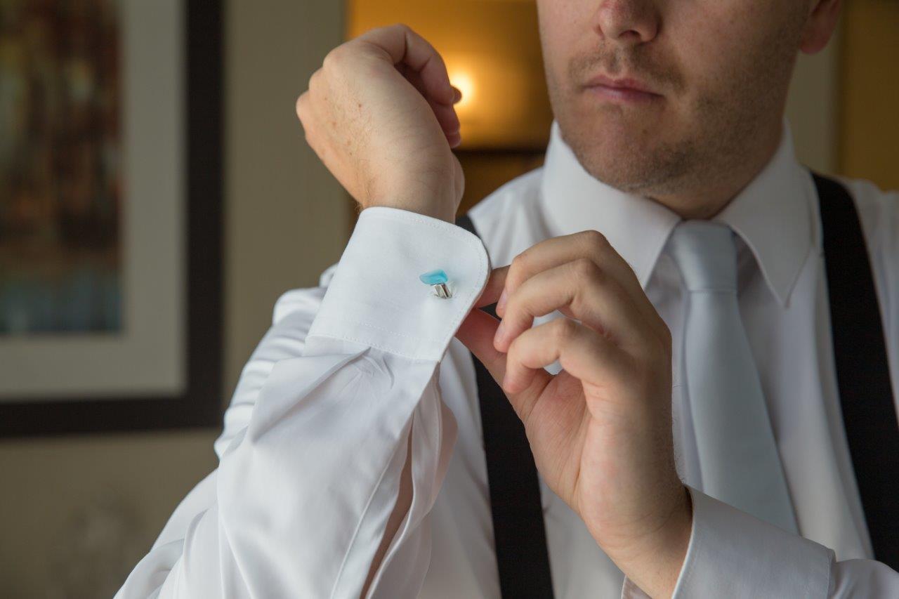Groom puts on seglass cufflinks