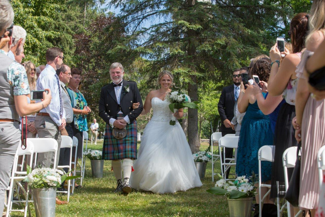 A father in a kilt walks his daughter down the aisle
