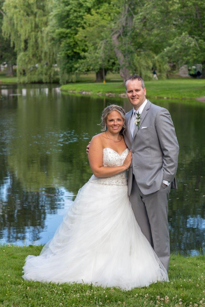 The bride and groom pose for a photgraph by the lake