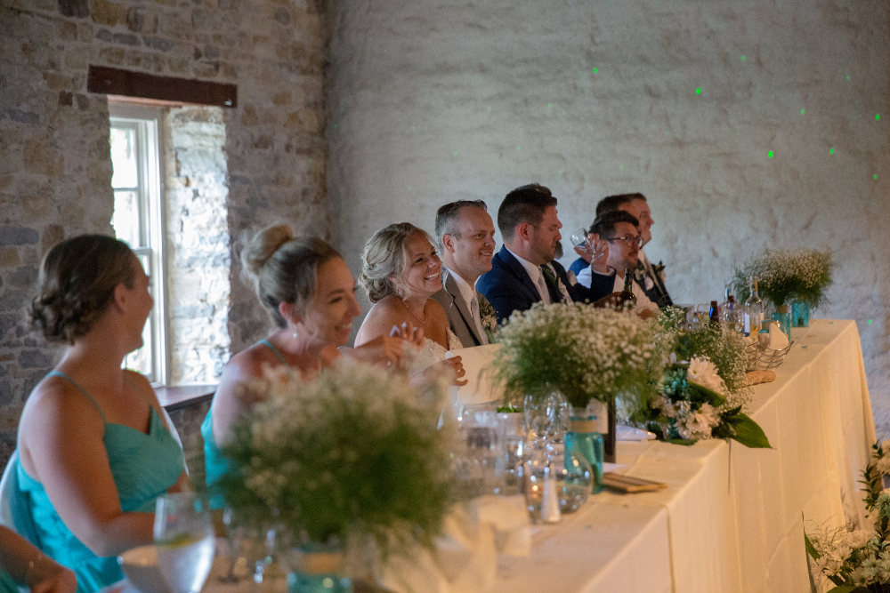 Head table at wedding reception, with baby's breath and seaglass centrepieces