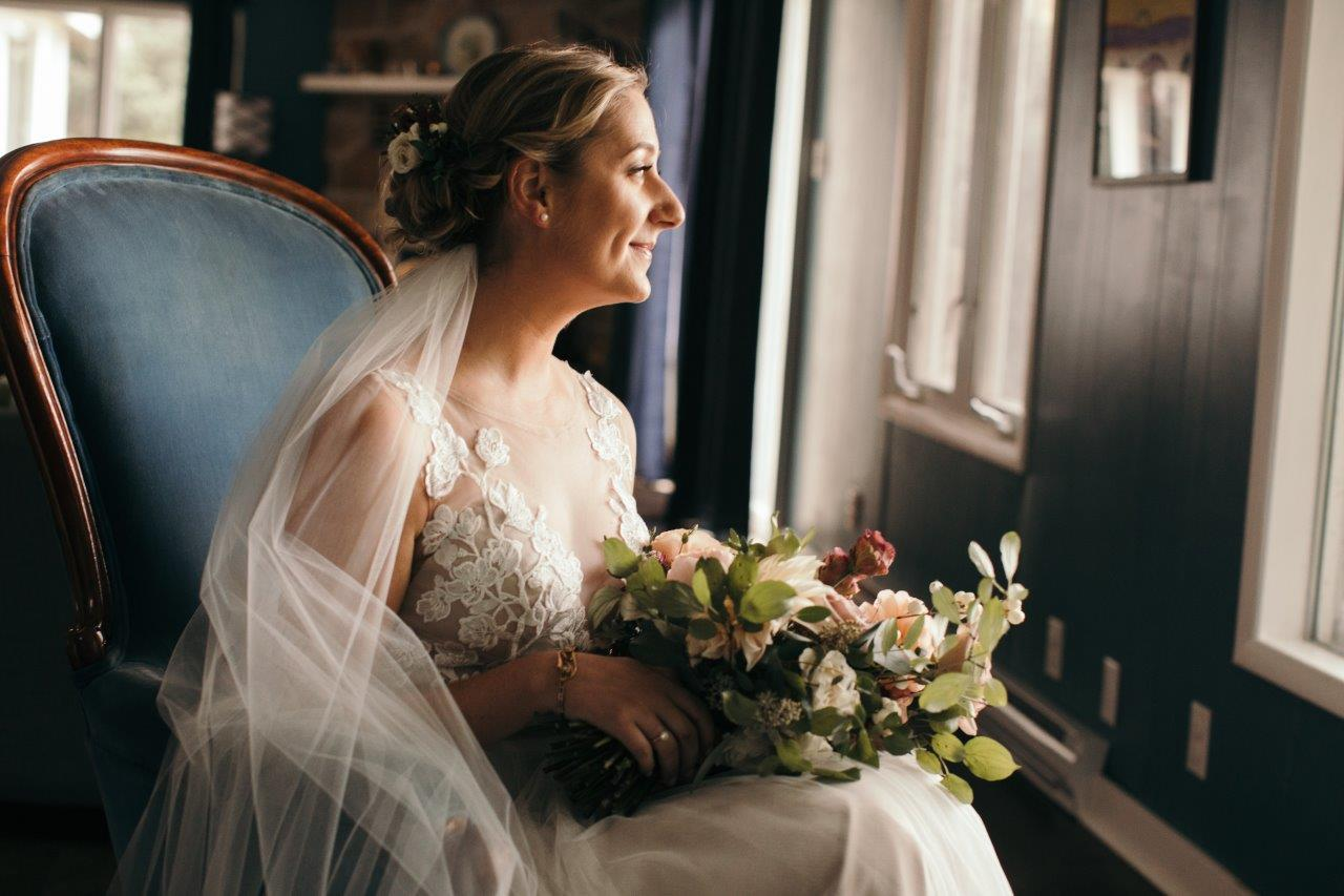 Bride holding a bouquet of flowers looking out the window