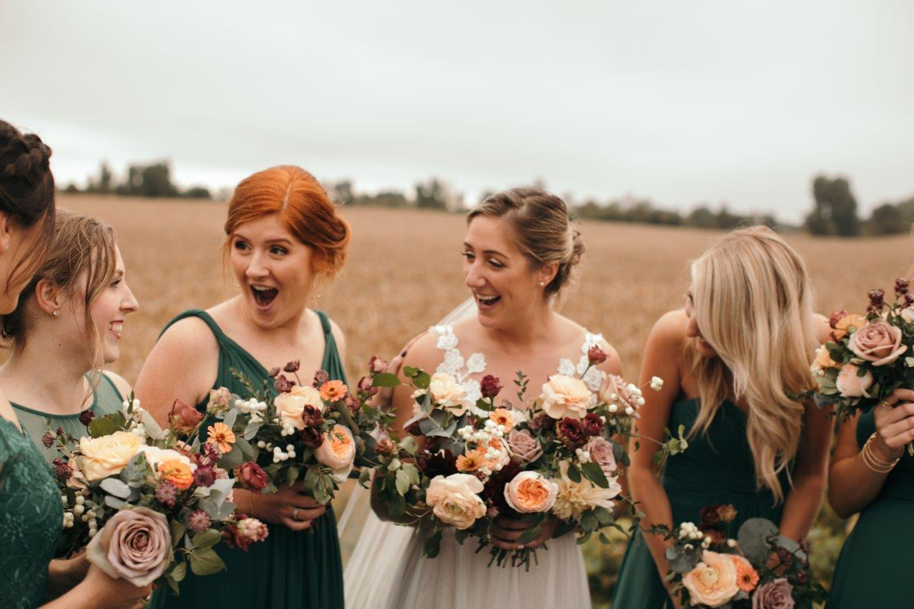 Bride talks with her bridesmaids in a wheat field