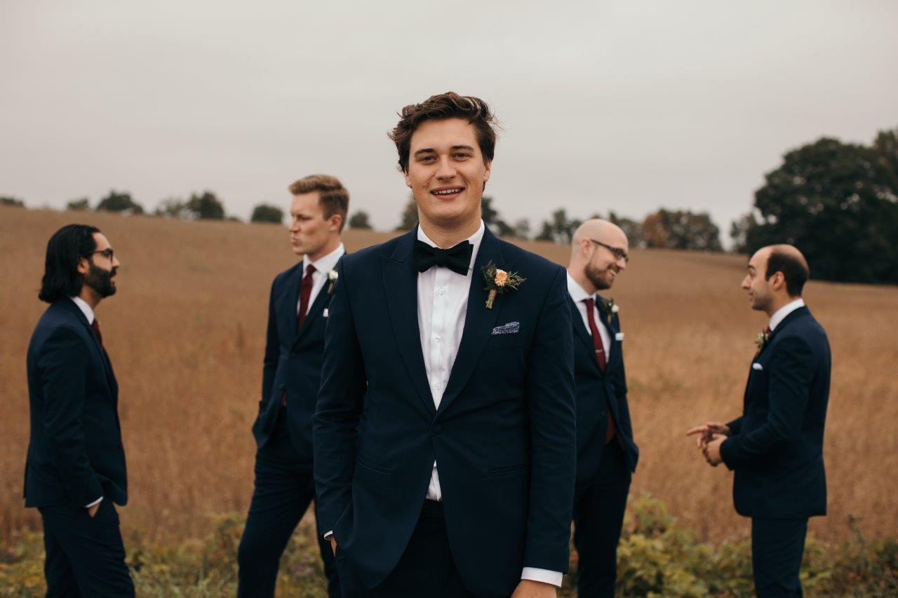 Groom walks towards camera with groomsmen in the background