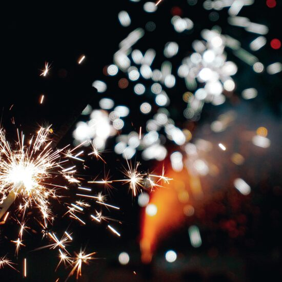 Close up of lighted sparkler with fireworks in the background