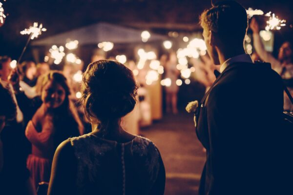 Two people look on at an outdoor nighttime wedding illuminated by sparklers.