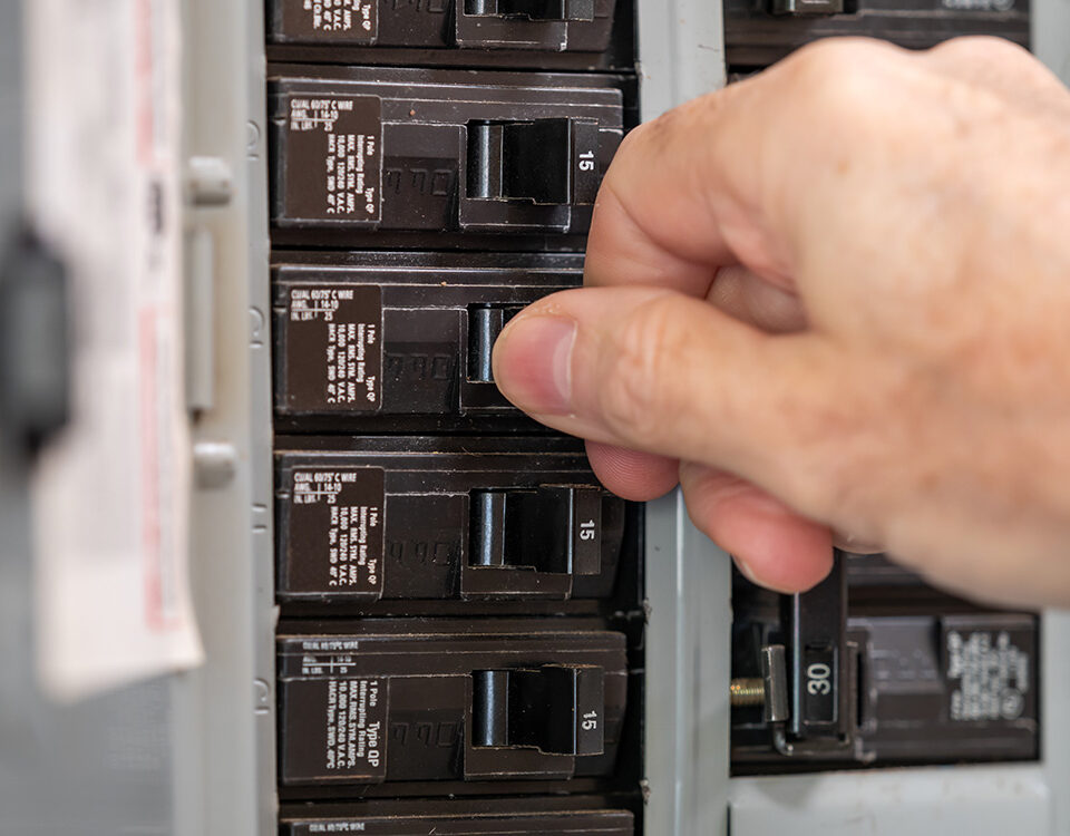 licensed electrician working on breaker box