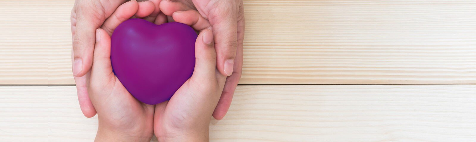 A young hand holding a purple heart, while an older hand holds onto both