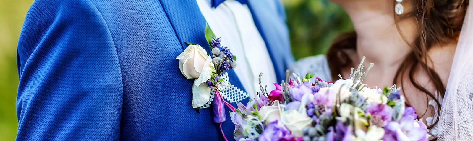 A bust shot of a married couple with a bouquet of flowers in the foreground