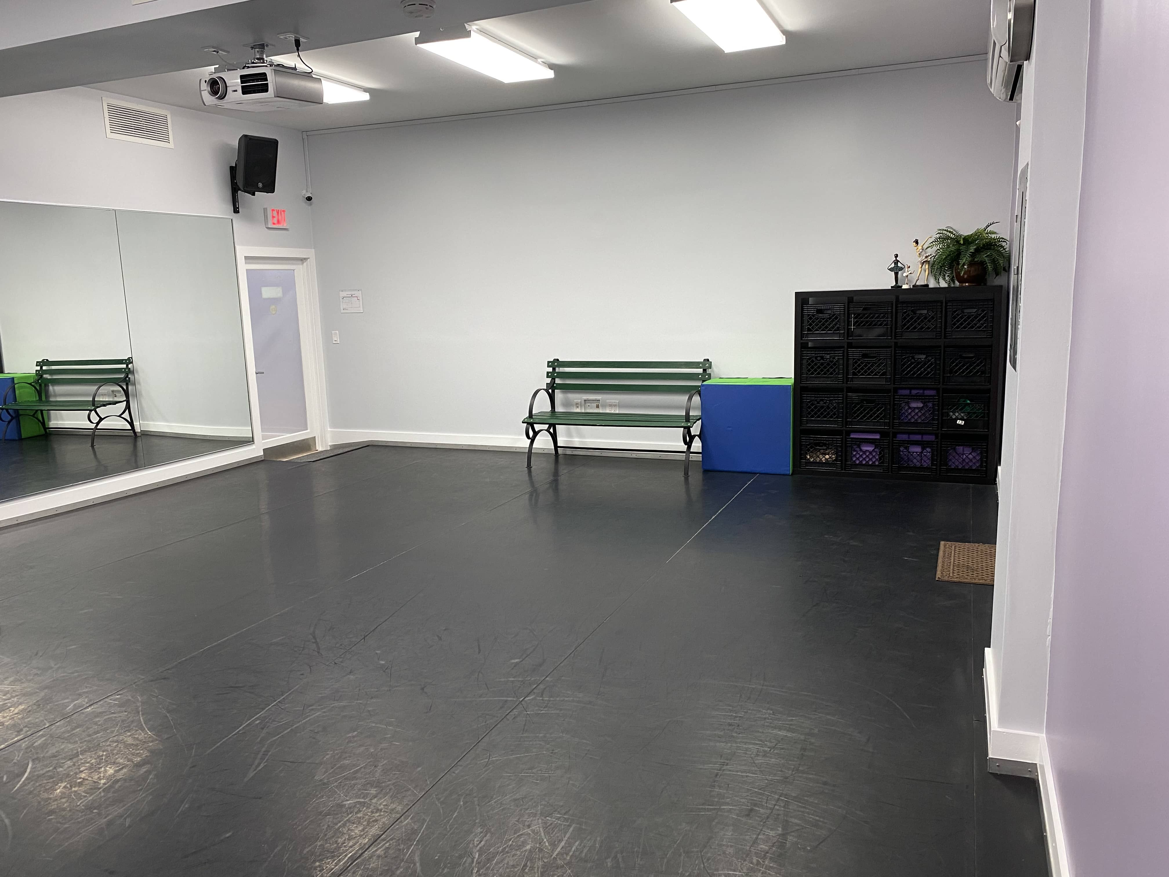 Another angle showing the inside of Creativo Dance Studio with padded dance floor and mirror on the wall