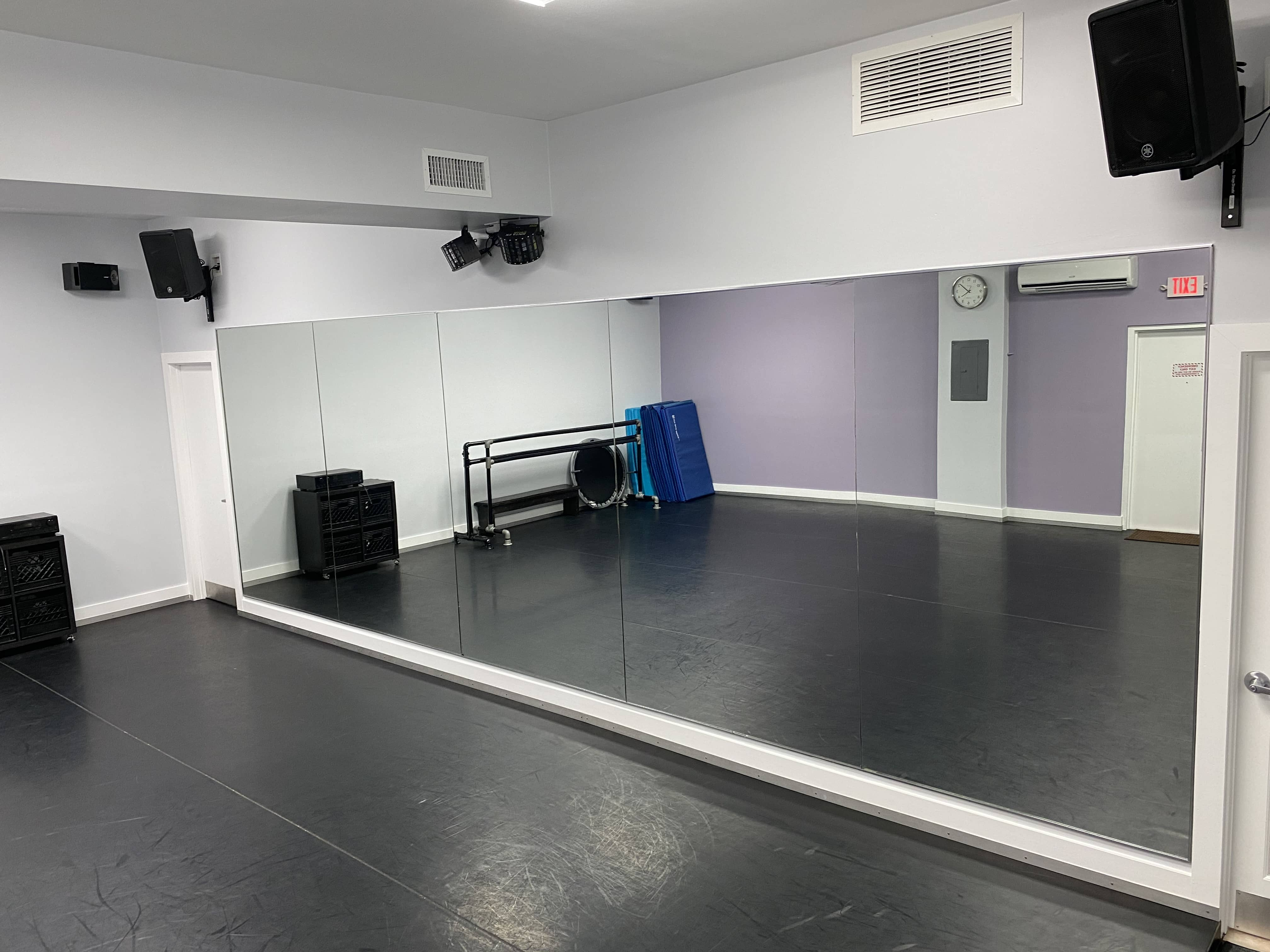Dance studio with padded floor and mirror facing the dance floor