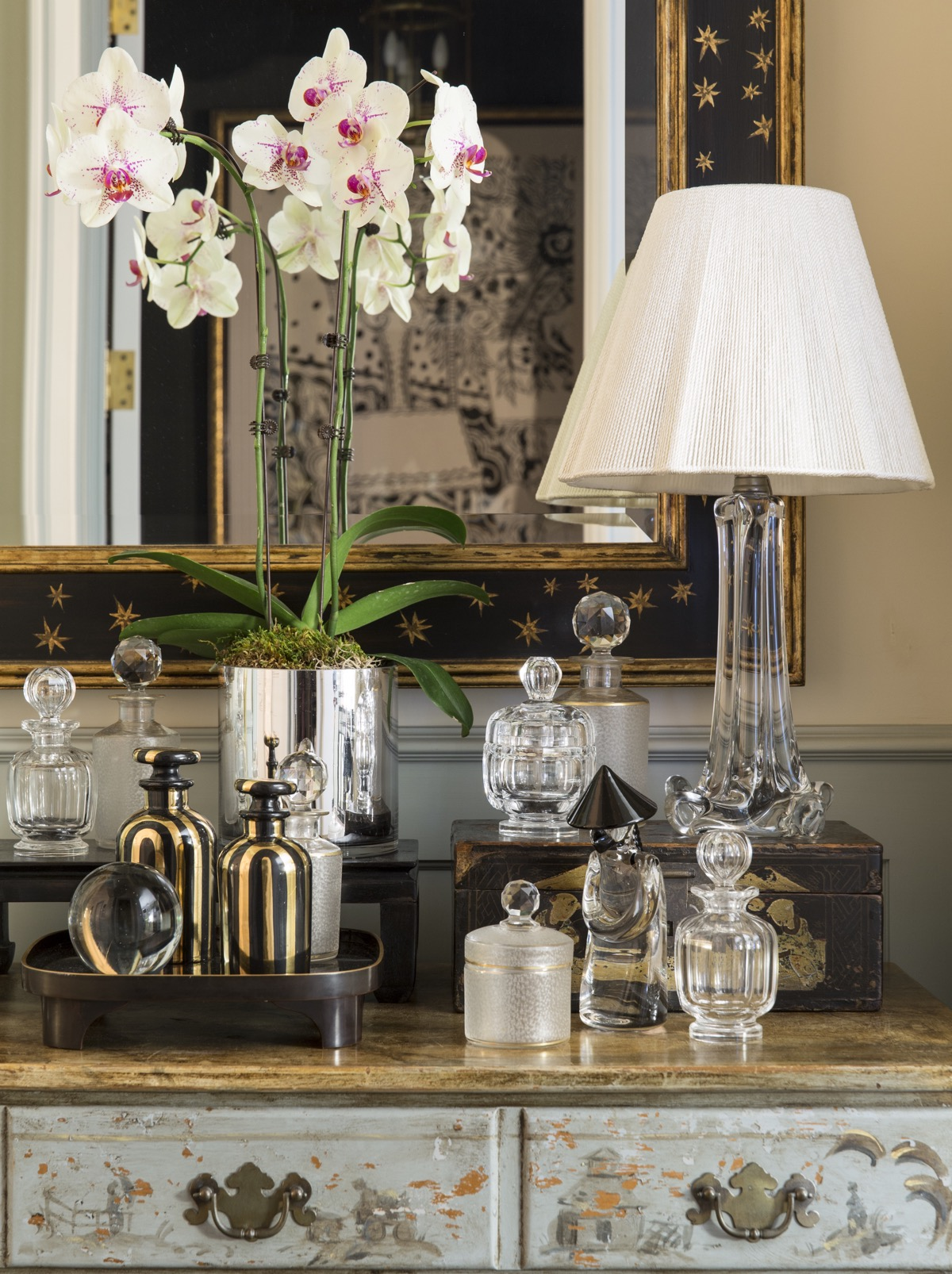 Antique perfume bottles sitting on top dresser with lamp in front of mirrow