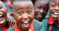A Uganda Child smiles with delight