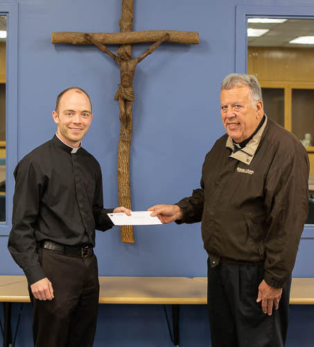 Father Tyler Tenbarge, left, Chaplain and Director of the Diocese of Evansville's Father Deydier House of Discernment, accepts a $500 check to support the house from Father John Boeglin, who presented the donation on behalf of Knights of Columbus Council #1584 in Jasper. Father Boeglin is pastor of Holy Family Parish in Jasper and Chaplain of Council #1584. Photo by Matt Potter, special to The Message