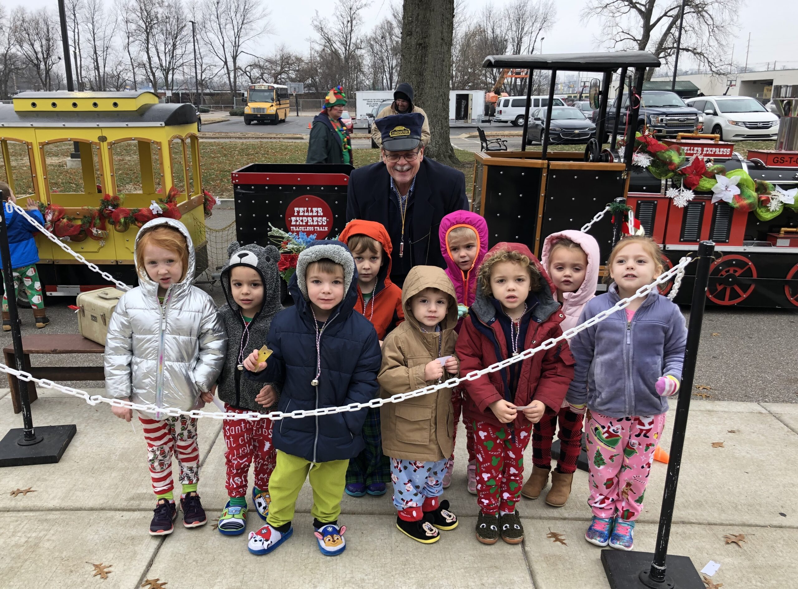 "The Preschool and Pre-K students of Holy Rosary School's Totten Hall were excited to board the Polar Express recently while wearing their Christmas pajamas. Our conductor, Parish Manager Joe Holtz, shown with the students, punched their golden tickets while blowing his whistle and shouting ""All aboard!"" After the round trip they enjoyed hot chocolate and cookies. Submitted photo"