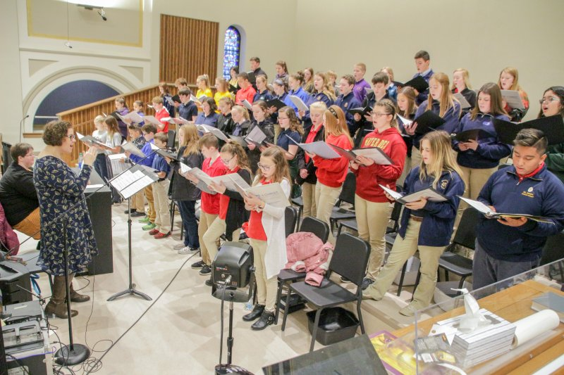 Led by Laura Litwiler of Washington Catholic High School, at the keyboard, and her sister Heidi, of Rivet High School, students from each of the 26 diocesan Catholic schools served as the choir for the Mass. The Message photo by Tim Lilley