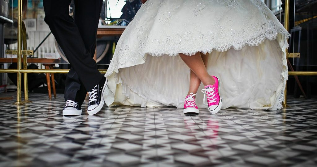 bride a groom's feet wearing black converse and pink converse with suit and white dress