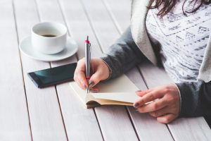 girl sat at table writing in a notebook with a coffee next to her