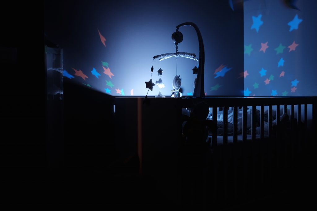 a cot in the dark with a night light over it