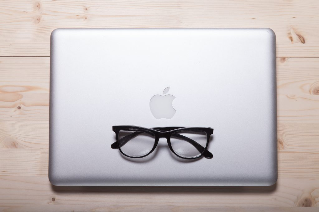 closed macbook with a pair of black framed glasses on top