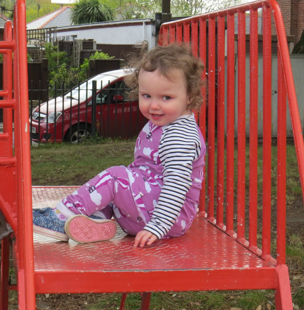 Alyssa sat on the red frame of a slide in a big black and white outfit with balloons on smiling at the camera with railings grass and a car in the background