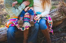 a man woman and child in jeans and boots sat on a log with a crochet blanket