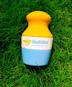 a yellow white and blue plastic solar buddies applicator with the lid on sat on grass