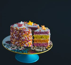 a 4 layered cake in pink yellow and orange seperated with white buttercream and covered on the outside in buttercream then multicoloured sprinkles and stars with a slice of the cake cut and pulled out slightly on a cake stand on a completely black background