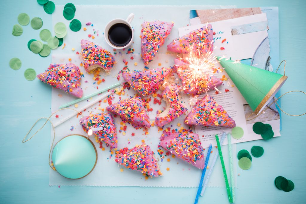 pink triangles of cake covered in sprinkles on white floorboards surrounded by green and blue straws and party hats and a cup of cola in the middle and a sparkler lit on the right