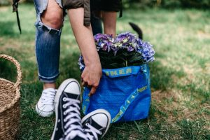 a pair of converse on grass behind it a blue ikea bag with flowers poking out the top being picked up by a person in white trainers and ripped jeans