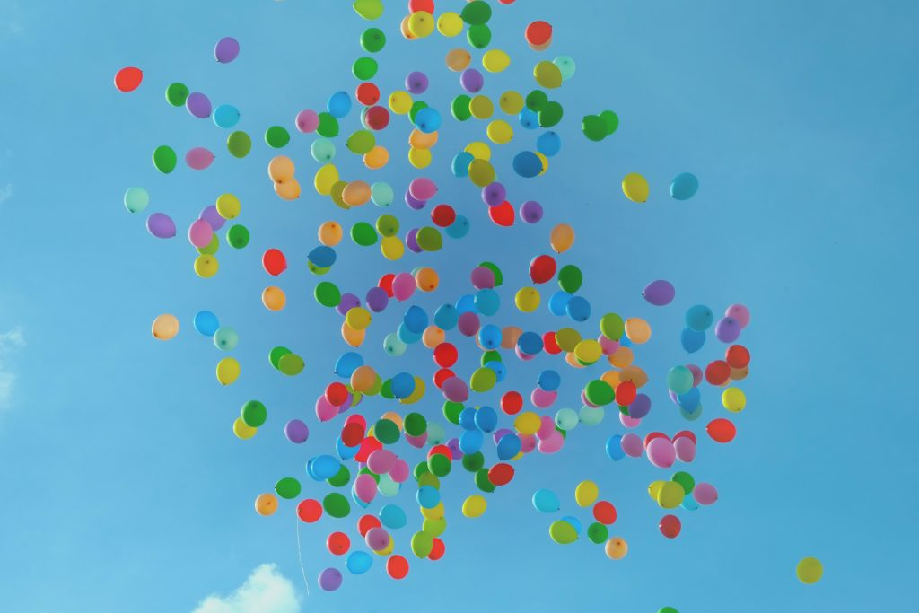 hundreds of balloons in every colour of the rainbow up high in the clear blue sky floating away