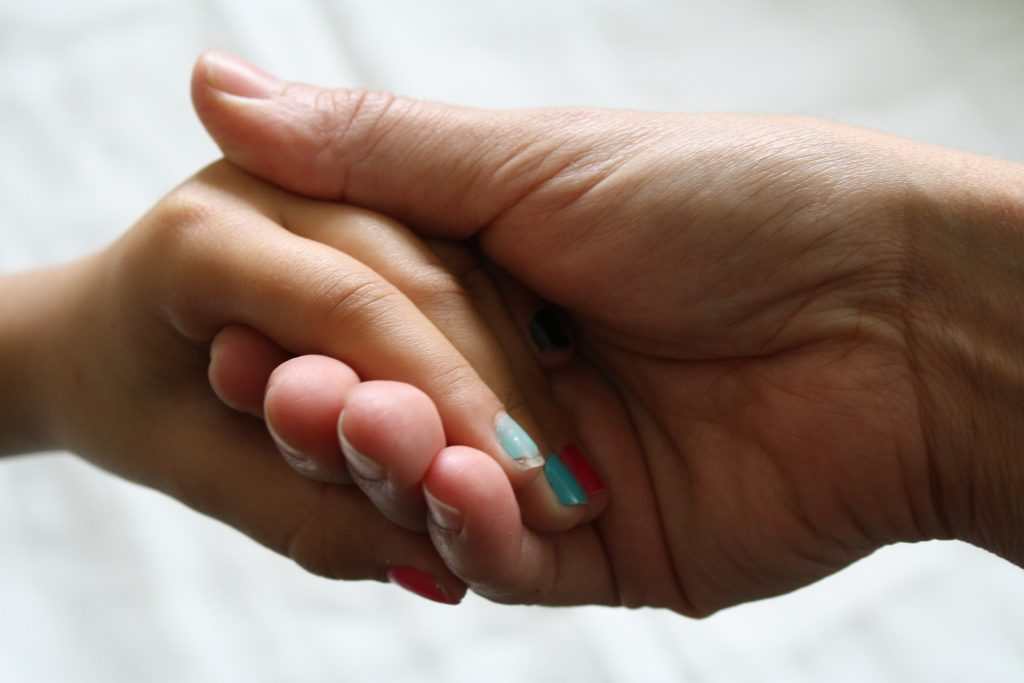 two hands holding. one with chipped aqua nail varnish on