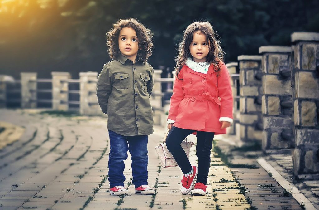two children on a pavement in coats looking at the camera