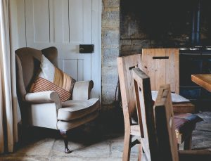 a wooden floor and bare brick walls a brown wing backed arm chair in the corner with a multi-tonal brown cushion on and to the right 4 wooden dining table chairs