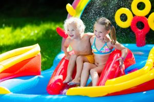 two children at the top of an inflatable slide in a paddling pool on a sunny day. costumes and pool red yellow and blue