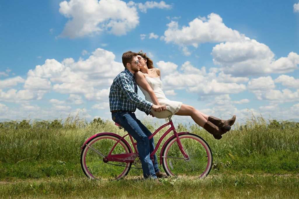 a man riding a bicycle with a woman on the handle bars on a blue sky day