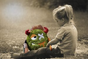 a black and white photo of a little blonde girl sat on a path with a coloured toy that is sad with lots of bandages on