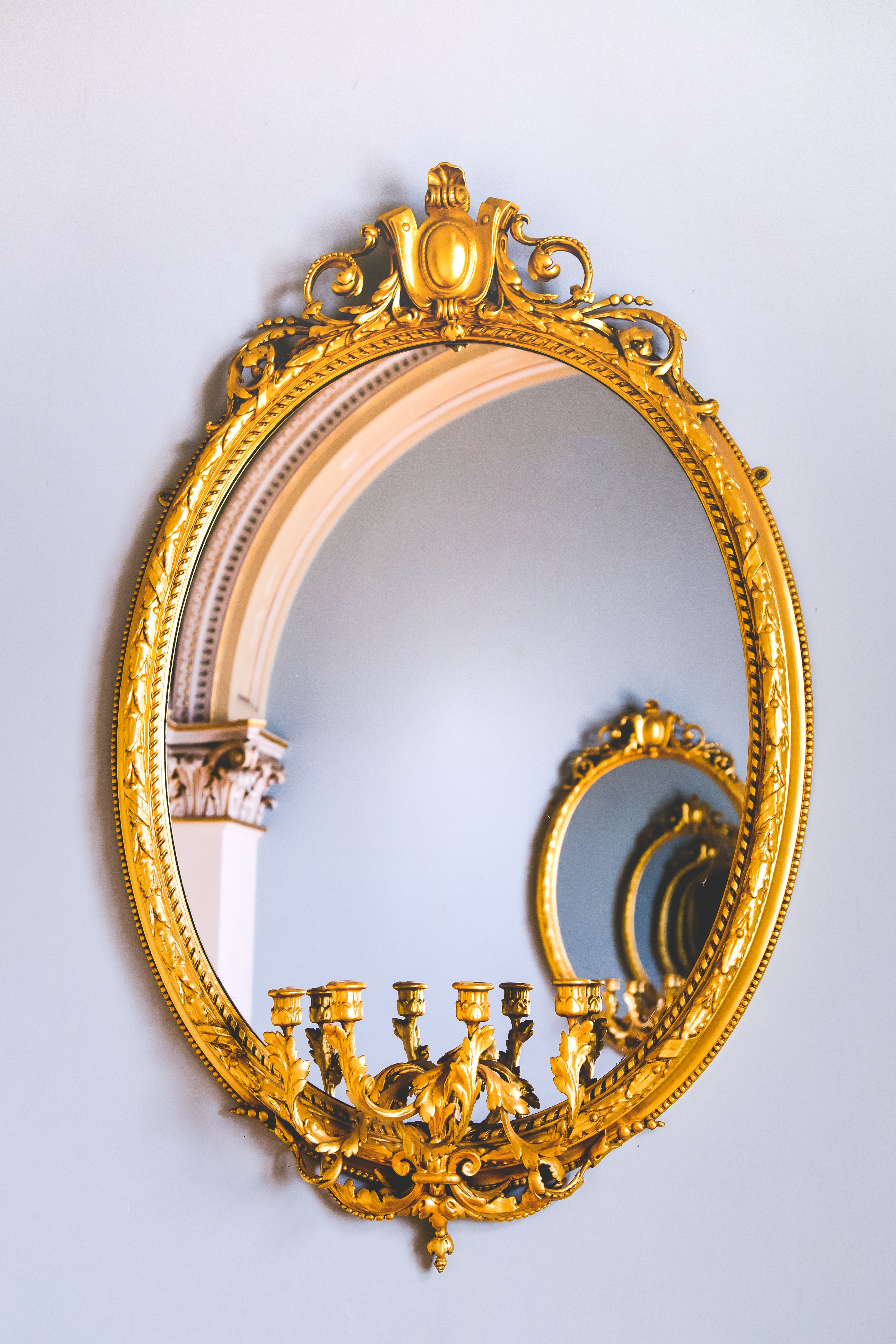 a gold oval mirror on a white wall and in the reflection are several more of the same mirror