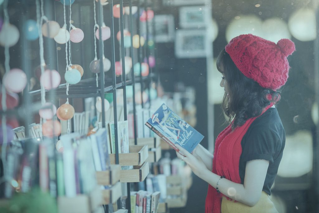 a woman stood at a wall of books reading one and laughing wearing a red hat and scarf