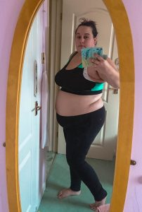 me in a cropped gym top and leggings showing my flab in a mirror
