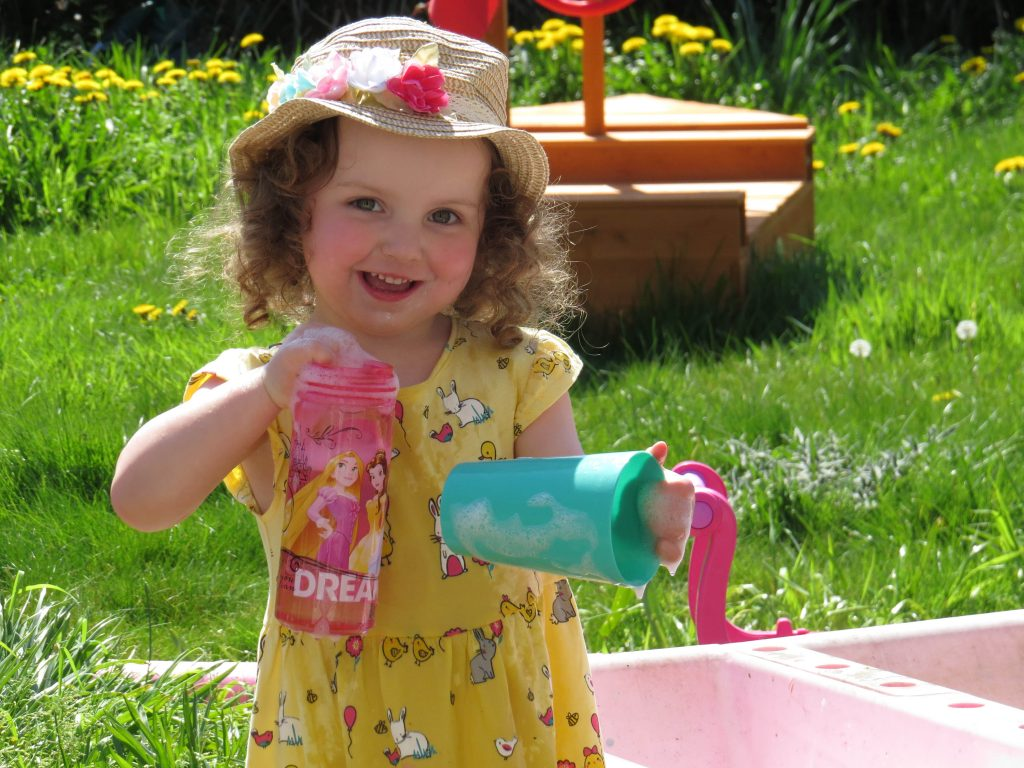 alyssa playing at a water table in a yellow dress and summer hat smiling at the camera