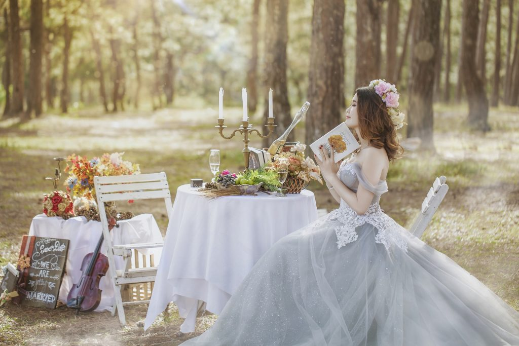 a bride sat a table with champagne and cheese in a garden