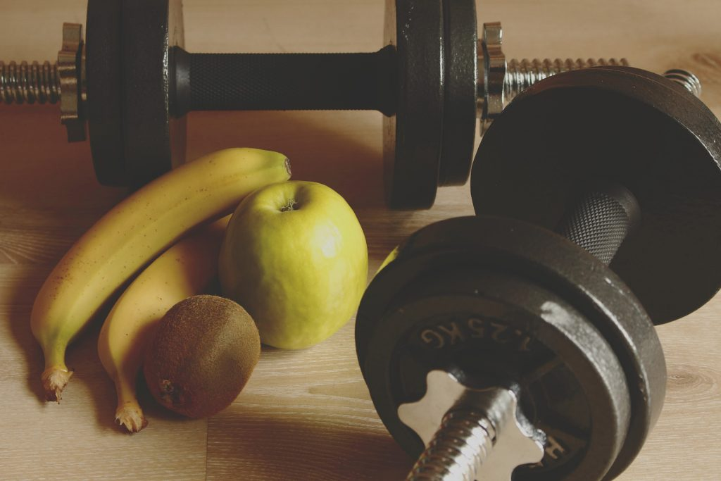 a set of dumbells and some bananas and apples