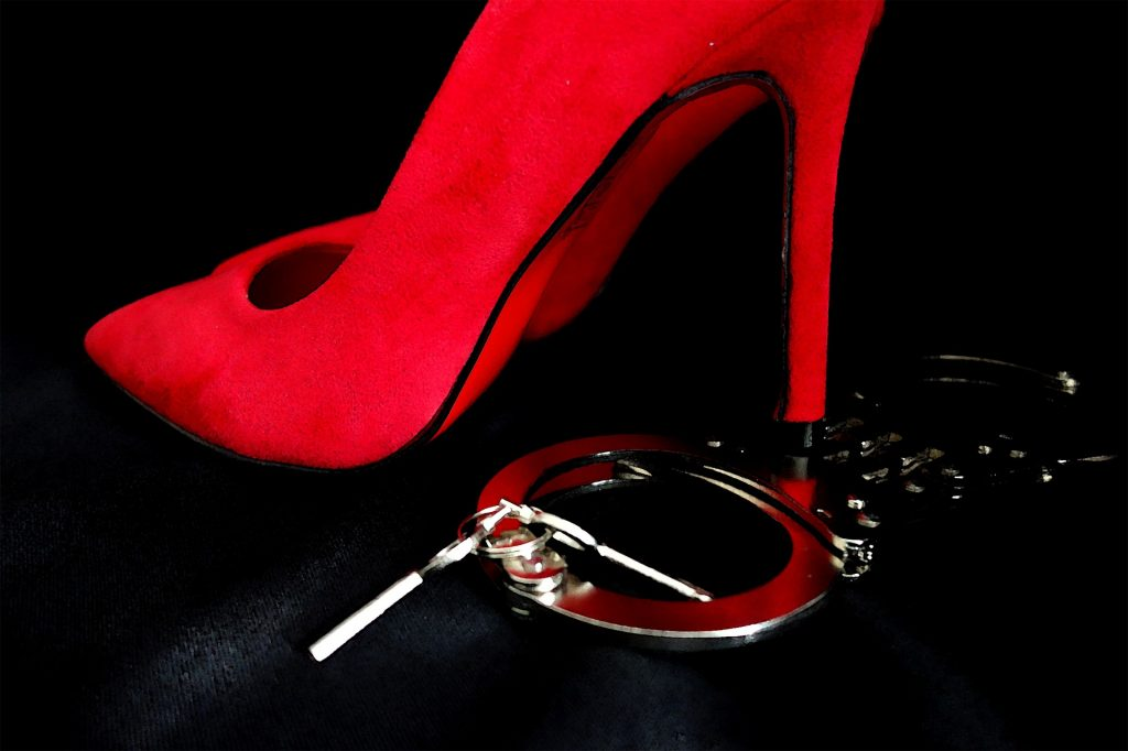 a red stiletto above a pair of handcuffs