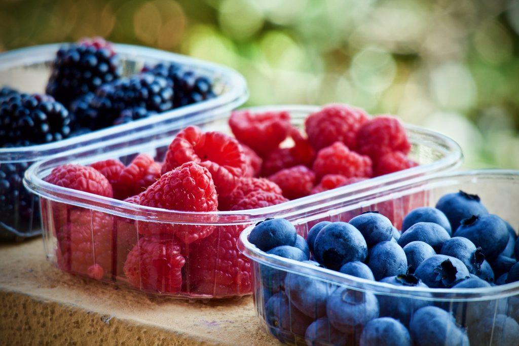 three punnets of fresh fruit on a bench - raspberries, blueberries and blackberries