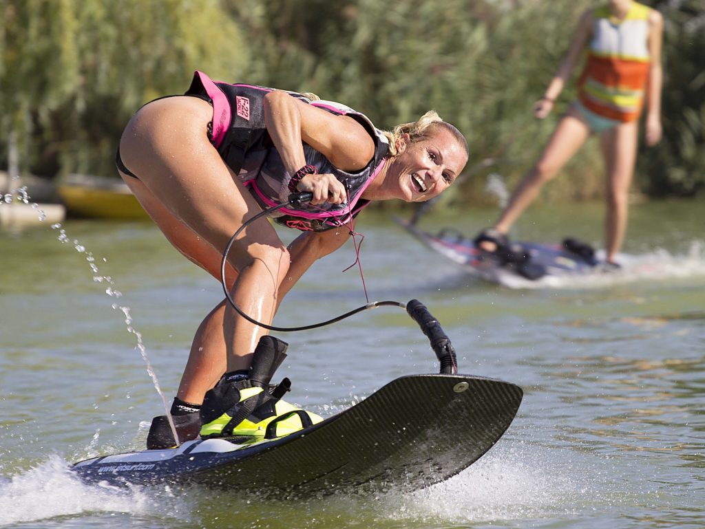 a woman smiling on a water ski in the middle of the water