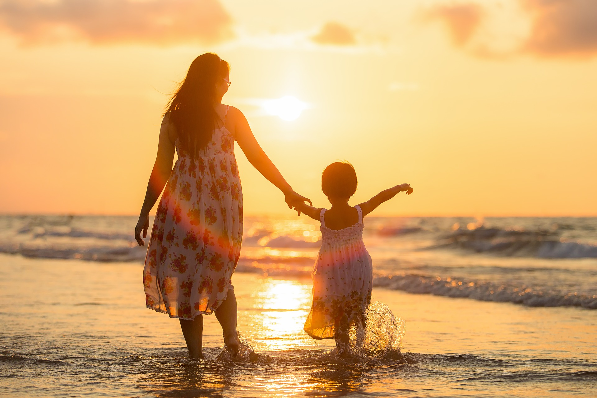 a mother and daughter holding hands walking along the beach at sunset