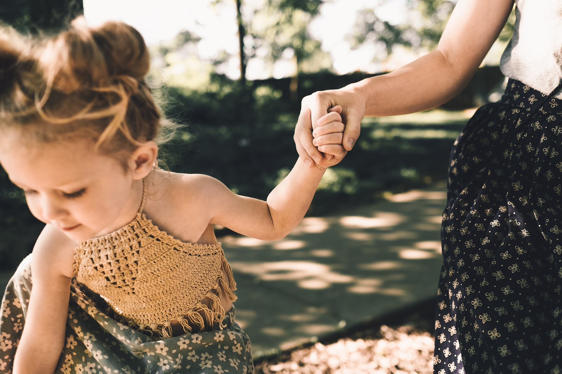 a woman holding a child's hand outside