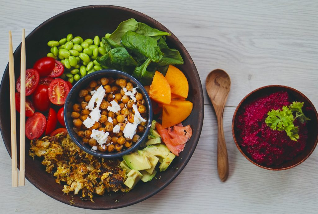 an above shot of a buddha bowl salad with a spoon and beetroot humus next to it