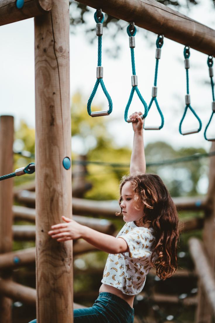 little girl swinging on monkey bars